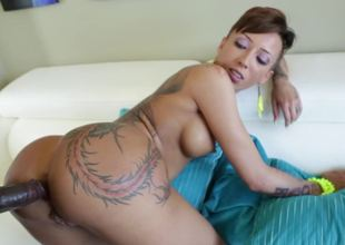 A bitch that has hot tattoos is riding a big black dick on the sofa