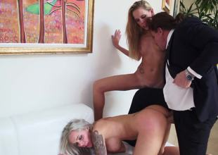 A blonde with some large fake marangos is getting fucked in a trio