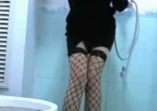 girl in sex underware strips in the bathroom, precipitation coupled with rubs her trimmed pussy.