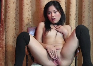 Charming Oriental strips and fucks her grungy crack with a toy