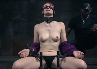 Collared and tied redheaded beauty in a dungeon