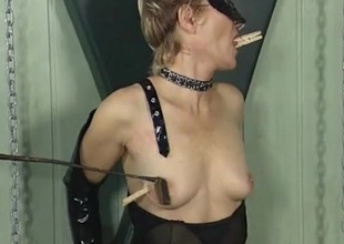 Clothes pins on make an issue of titties of a girl approximately black latex