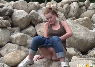 Parsimonious pussy gal relative to jeans pees on the rocks