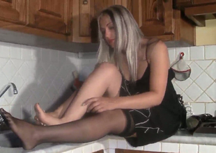 Hot blonde bitch Marlene  takes off the stockings in the kitchen