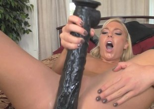 A blonde that is filled with lust is riding a large huge dildo