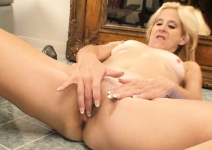 Excited blonde older lady with sexy special lies on the floor identity card her bald pussy
