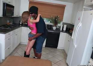 Petite ivory girl Natasha White in pink brassiere and hot shorts drops in excess of her knees in the middle of the kitchen and acquires her mouth filled with insidious monster cock. He stretches her mouth to the max with his large pole