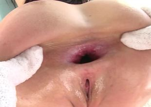 A brunette that loves anal is covered with oil and she's fucked